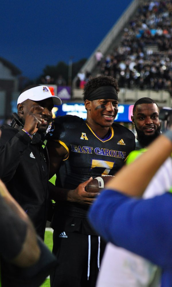 Zay Jones, with head coach Scottie Montgomery (left) and Justin Hardy (right) poses for pictures after being recognized for his record-breaking career during a break in action Saturday afternoon. (Bonesville Staff)