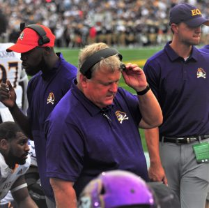Pirates defensive coordinator Bob Trott talks on his headphones after a third-down stop by his unit