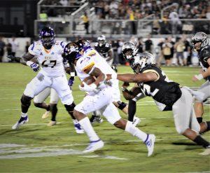 ECU running back Demetrius Mauney escapes the clutches of a Knights defender (Al Myatt photo)