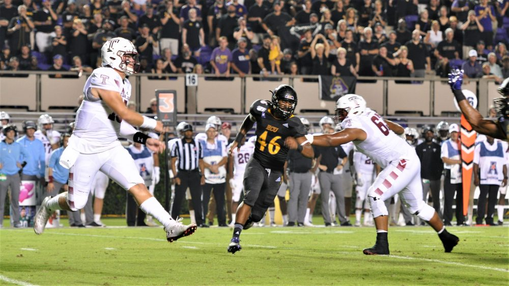 Temple quarterback Anthony Russo leaps to deliver a pass as Chance Purvis (46) rushes from his defensive end position for the Pirates. (Photo by Al Myatt)