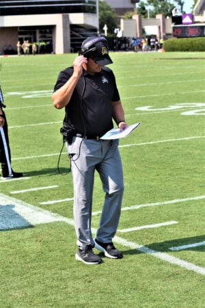 ECU coach Mike Houston focuses on his play sheet as he communicates with his staff.